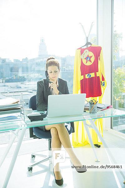 Geschäftsfrau arbeitet am Schreibtisch mit Superheldenkostüm hinter sich.