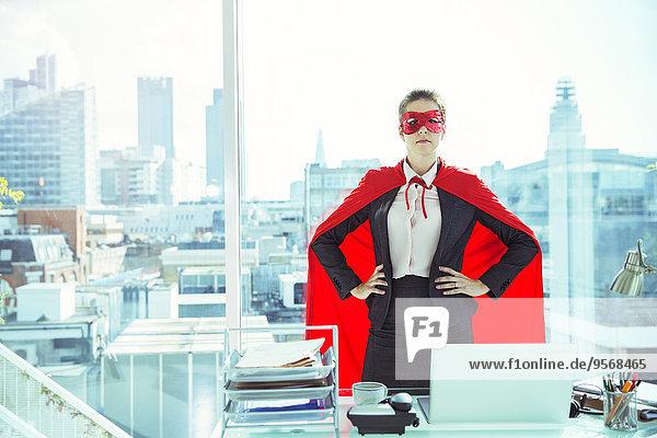 Geschäftsfrau mit Umhang und Maske im Büro
