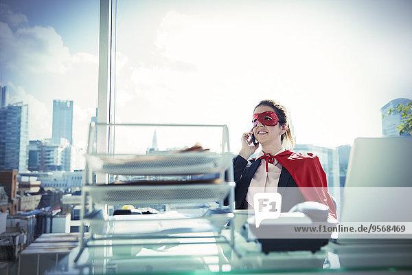 Geschäftsfrau in Cape und Maske beim Telefonieren am Bürotisch