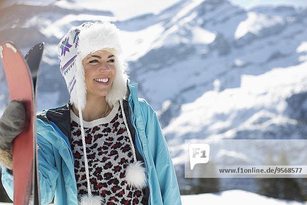 Lächelnde Frau mit Skiern am Berg