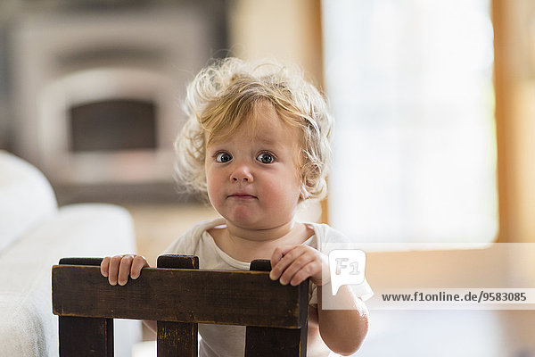 Caucasian baby boy standing behind chair in living room