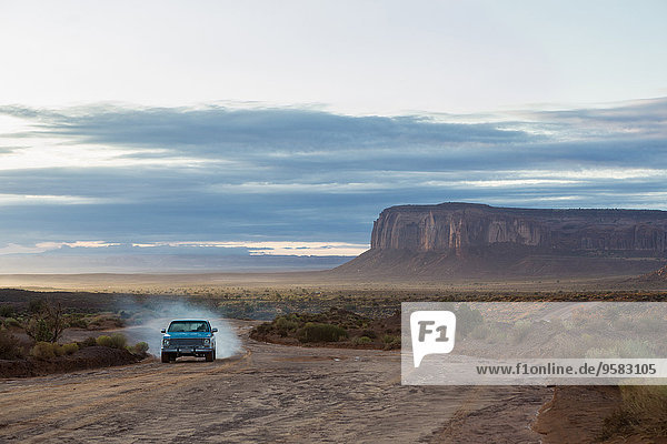 Car driving on dirt road in desert  Monument Valley  Utah  United States