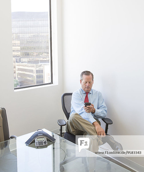 Caucasian businessman using cell phone at desk in office