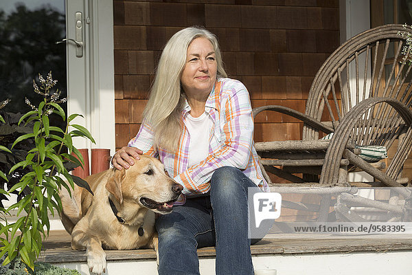 Older Caucasian woman petting dog on front porch