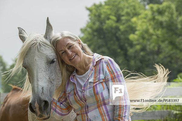 Older Caucasian woman petting horse outdoors