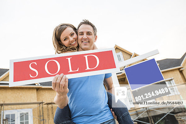 Caucasian couple holding sold sign near house under construction