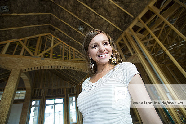 Caucasian woman smiling in house under construction