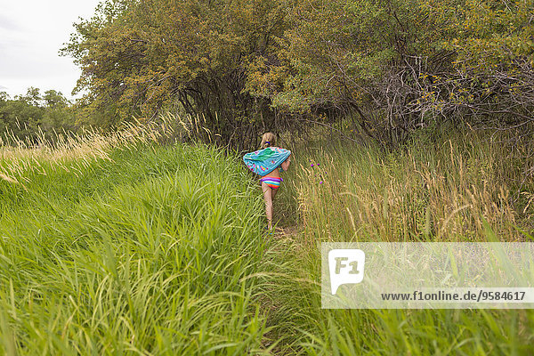 Caucasian girl carrying towel in tall grass