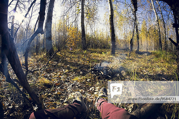 Fish-eye lens view of legs sitting by smoking campfire