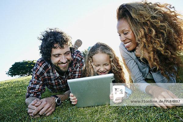 Family using digital tablet in grassy field