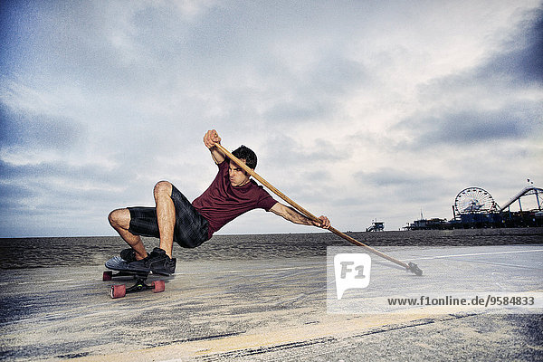 Caucasian man skateboarding with paddle pole at beach