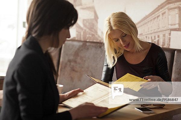 Women reading menus in cafe