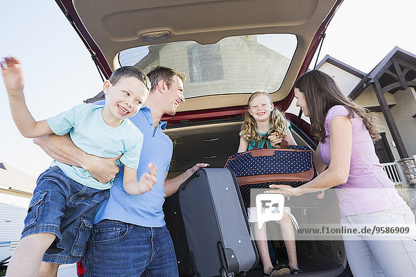 Caucasian family unpacking suitcases from car