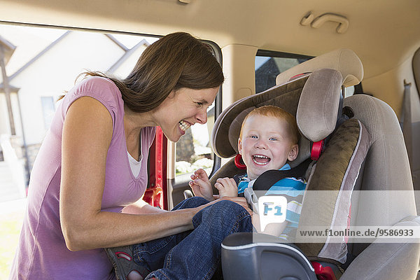 Caucasian mother fastening son into car seat