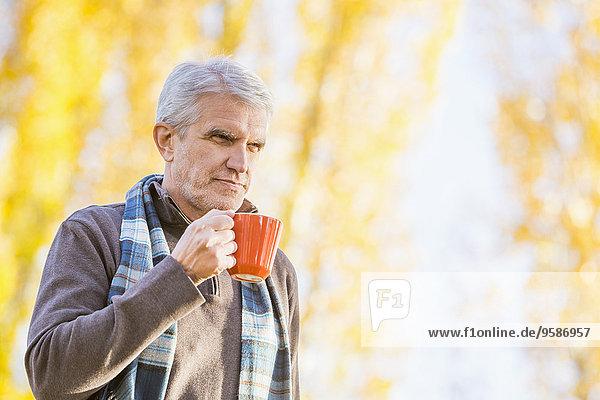 Older Caucasian man drinking coffee near autumn trees