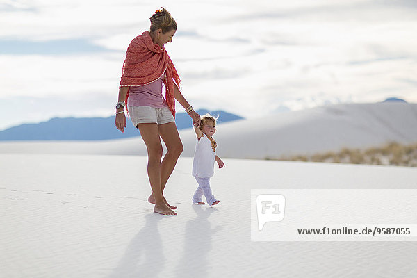 Caucasian mother and son walking on sand dune