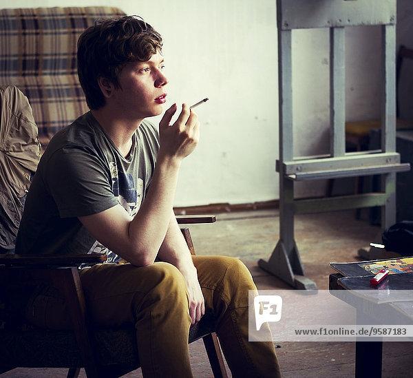 rauchen rauchend raucht qualm qualmend qualmt Europäer Mann Zimmer Zigarette Wohnzimmer
