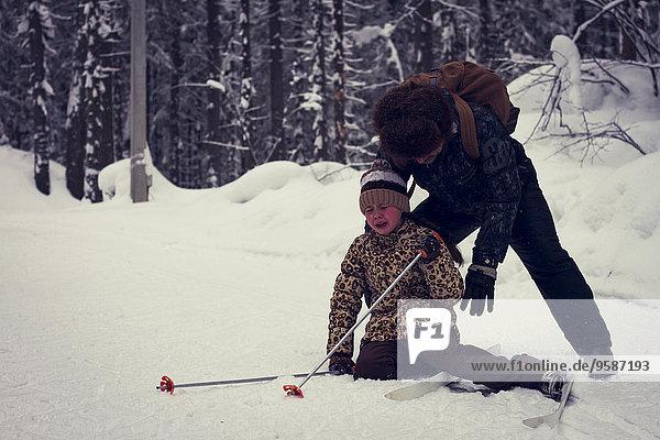 fallen fallend fällt Europäer Menschlicher Vater Hilfe Skisport Tochter querfeldein Cross Country Schnee