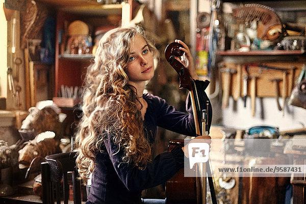 Caucasian teenage girl holding musical instrument in workshop