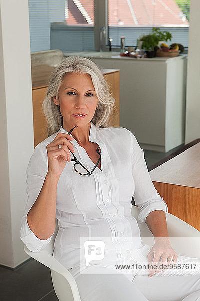 Porträt einer reifen Frau  die in ihrer Küche sitzt.