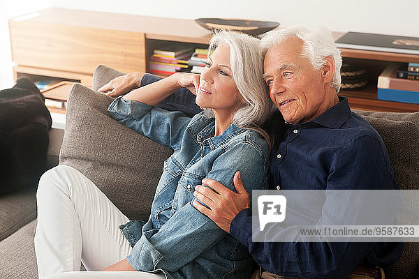Porträt eines liebenden älteren Paares  das Seite an Seite auf der Couch sitzt.