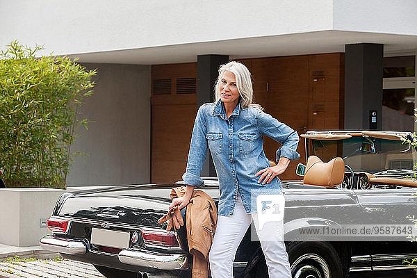 Reife Frau  die sich auf ein Cabriolet stützt.