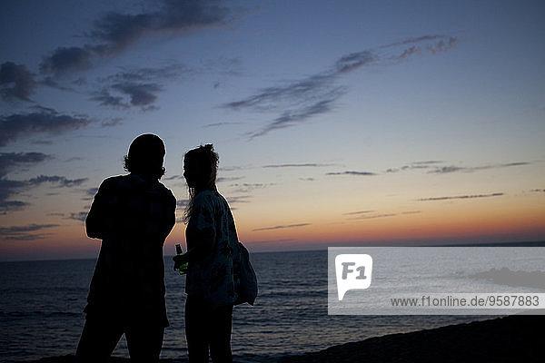 Frankreich  Aquitanien  Silhouette eines Paares  das das Meer in der Dämmerung beobachtet.