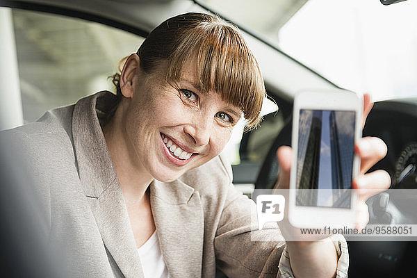 Porträt einer lächelnden Geschäftsfrau  die in einem Auto sitzt und ihr Smartphone zeigt.