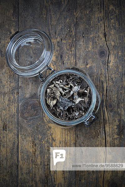 Einmachglas mit getrockneten schwarzen Pfifferlingen  Craterellus cornucopioides  auf dunklem Holz
