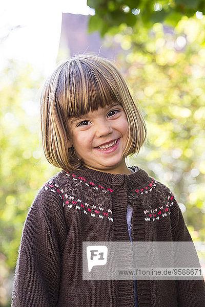 Portrait of smiling little girl wearing brown cardigan