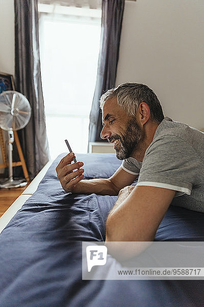 Smiling man lying on his bed looking at his smartphone
