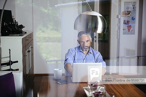 Geschäftsmann bei der Arbeit mit dem Laptop im Home-Office