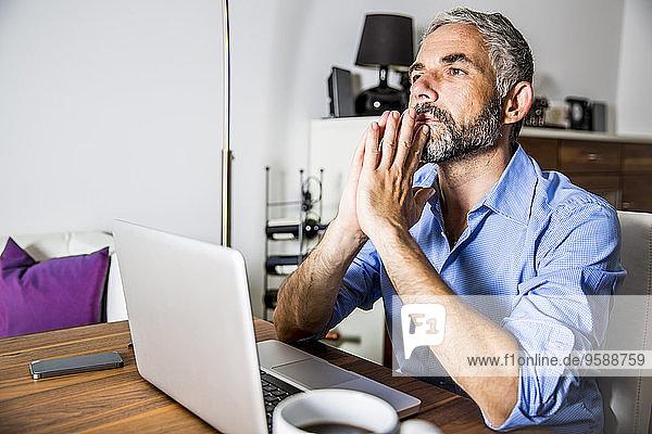 Porträt eines pansiven Geschäftsmannes  der mit dem Laptop im Home-Office arbeitet.