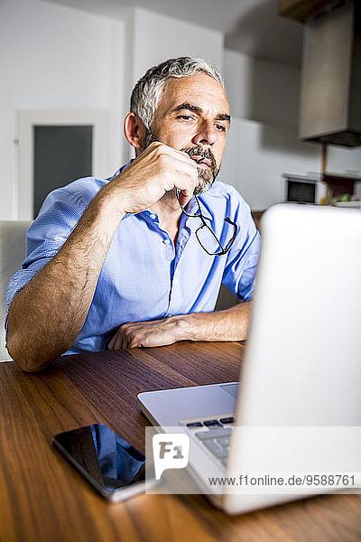 Nachdenklicher Geschäftsmann bei der Arbeit mit dem Laptop im Home-Office