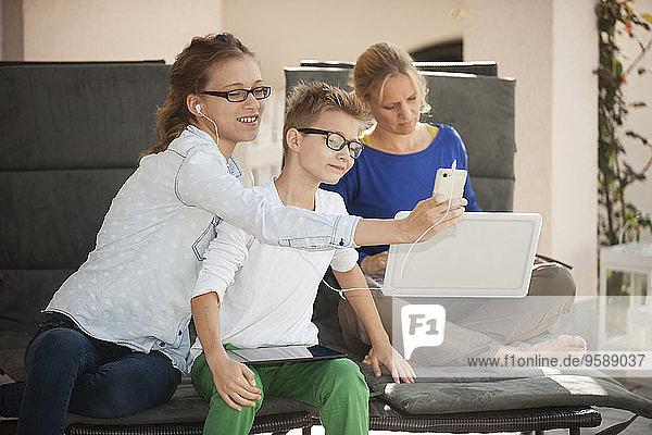 Mutter und ihre beiden Kinder entspannen sich mit digitalem Tablett  Smartphone und Laptop auf der Terrasse.
