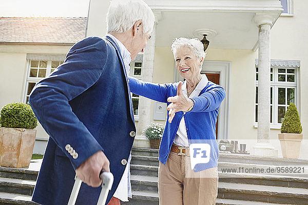 Deutschland,  Hessen,  Frankfurt,  Seniorenpaar vor der Villa,  Frau begrüßt Mann