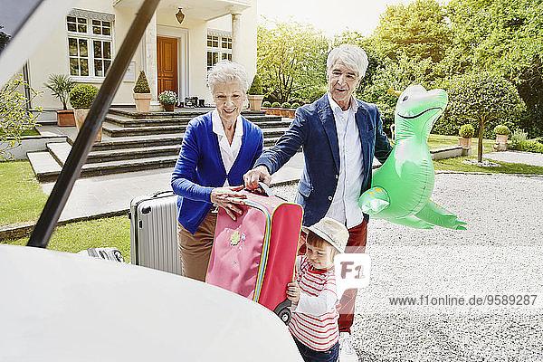 Großeltern mit Enkelin und Gepäck auf der Einfahrt