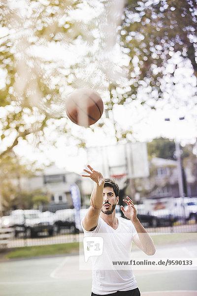 Junger Basketballspieler wirft Ball auf Basketballkorb Junger Basketballspieler wirft Ball auf Basketballkorb