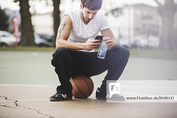 Junger Basketballer sitzt auf dem Ball und schreibt auf dem Smartphone. Junger Basketballer sitzt auf dem Ball und schreibt auf dem Smartphone.