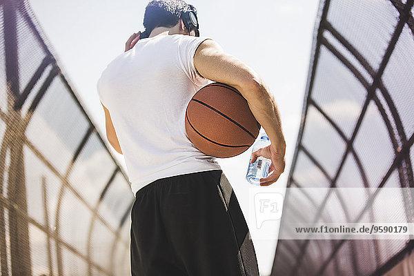 Rückansicht eines jungen Basketballspielers  der über eine Fußgängerbrücke läuft und Kopfhörer hört.