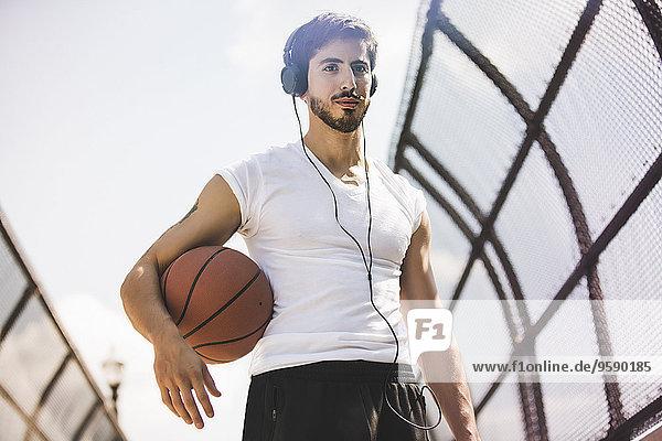 Junger männlicher Basketballspieler  der über eine Fußgängerbrücke läuft und Kopfhörer hört. Junger männlicher Basketballspieler, der über eine Fußgängerbrücke läuft und Kopfhörer hört.
