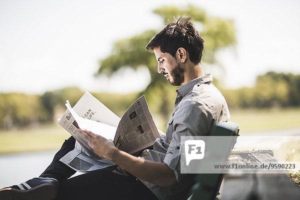 Junger Mann liest Zeitung auf Parkbank Junger Mann liest Zeitung auf Parkbank