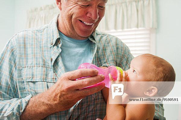 Großvater Flasche Fütterung Baby Enkelin auf Schoß im Wohnzimmer