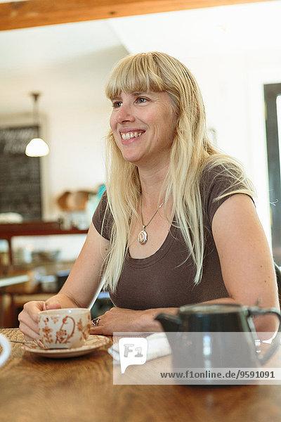 Mittlere erwachsene Frau trinkt Tee im Landhauscafé