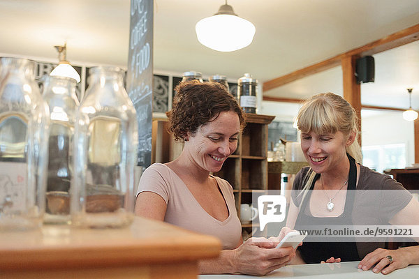 Female shop assistants looking at smartphone in country store