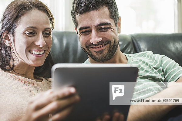 Paar mit digitalem Tablett auf dem Sofa