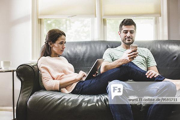 Paar mit digitalem Tablett und Smartphone auf dem Sofa