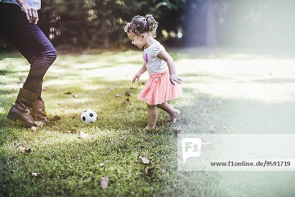 Kleines Mädchen beim Ballspielen im Garten