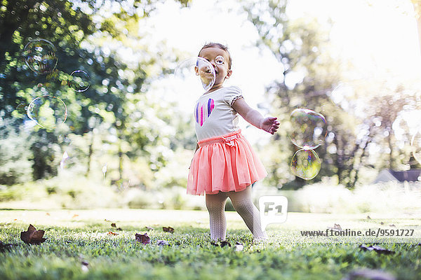Kleines Mädchen spielt mit Blasen im Garten Kleines Mädchen spielt mit Blasen im Garten