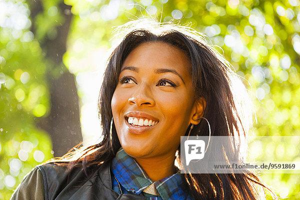 Junge Frau mit breitem Lächeln im Park